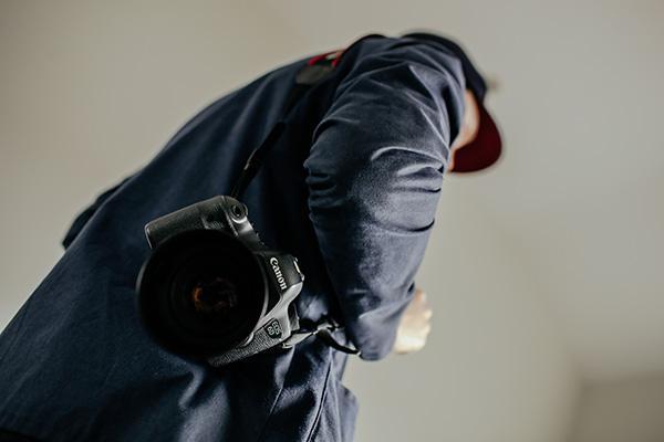 一眼レフカメラを肩にかけている